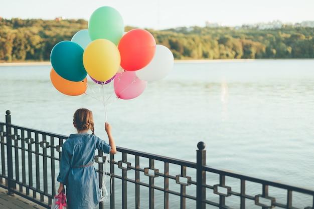 Ragazza ambulante che tiene i palloni variopinti e la valigia puerile