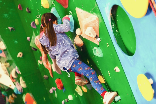 Ragazza arrampicata sulla parete pratica interna