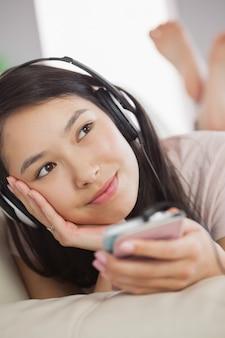 Ragazza asiatica allegra che si trova sul sofà e che ascolta la musica con lo smartphone che distoglie lo sguardo