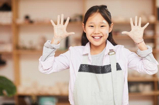 Ragazza asiatica allegra in classe di ceramica