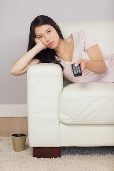 Ragazza asiatica annoiata che si trova sul sofà che guarda tv