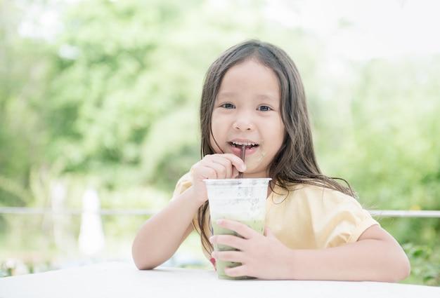 Ragazza asiatica carina bere tè verde al latte ghiacciato