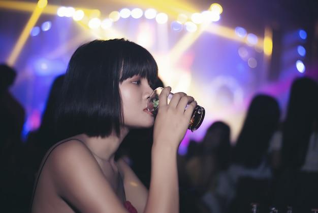 Ragazza asiatica che beve birra in un bar