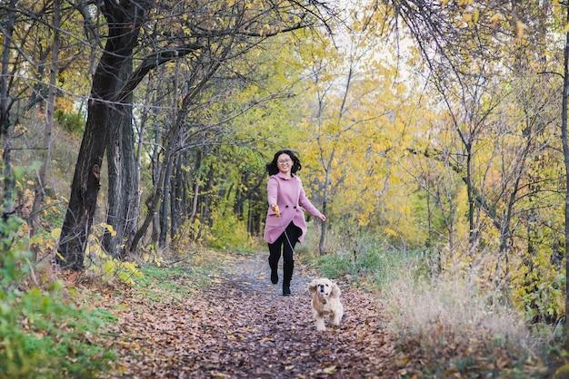 Ragazza asiatica che cammina con il suo cane nel parco. una ragazza corre dietro a un cane