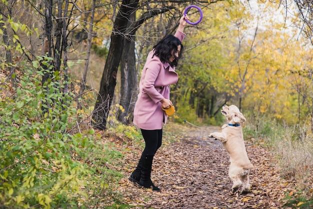Ragazza asiatica che gioca con il suo cane nel parco.