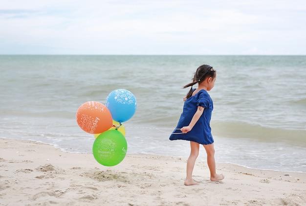 Ragazza asiatica che gioca gli aerostati sulla spiaggia