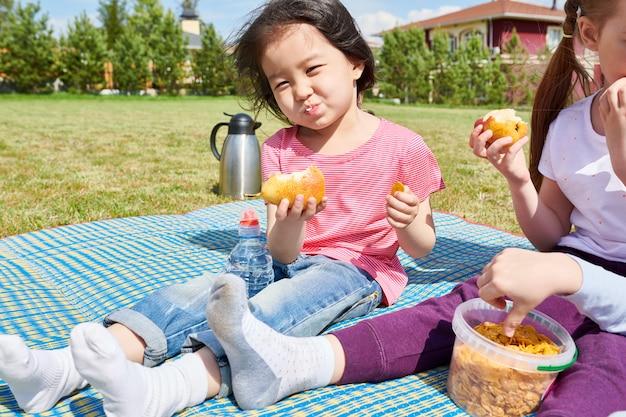 Ragazza asiatica che gode del picnic sul prato inglese
