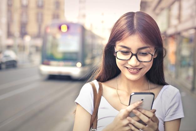Ragazza asiatica che manda un sms sulla via