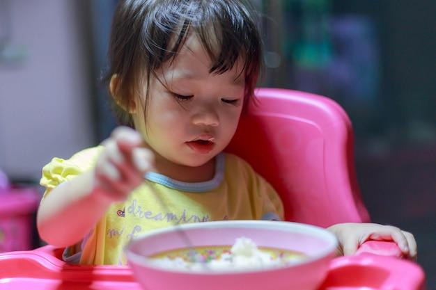 Ragazza asiatica che mangia le salsiccie fritte nella ciotola di alluminio vicino alla finestra a casa