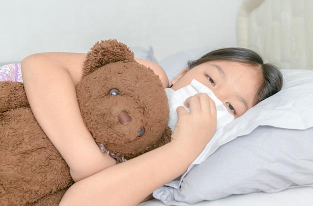 Ragazza asiatica che soffia il naso dal tessuto