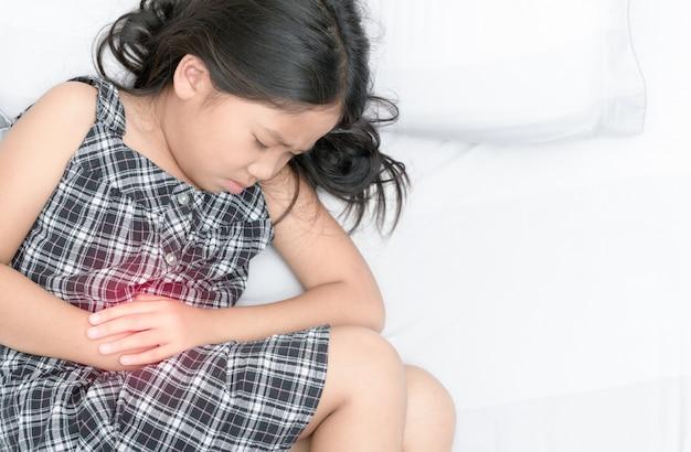 Ragazza asiatica che soffre di mal di stomaco