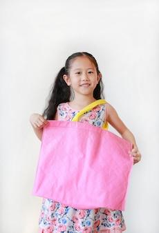 Ragazza asiatica che tiene una borsa rosa
