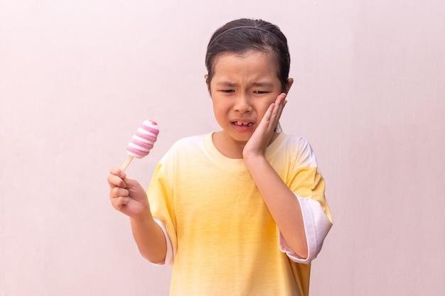 Ragazza asiatica con i denti ipersensibili che mangia mangiando un ghiacciolo congelato variopinto di estate
