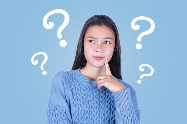 Ragazza asiatica con punti interrogativi su sfondo blu