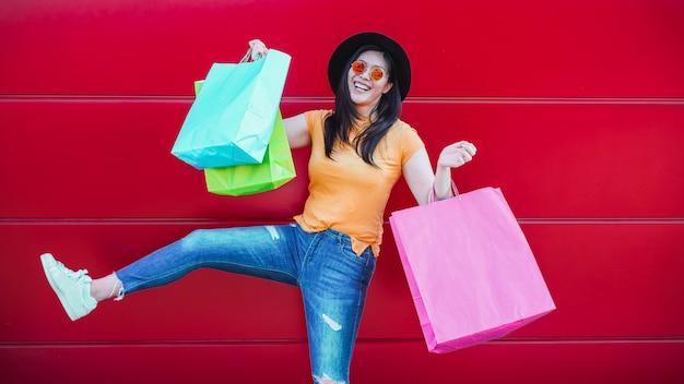 Ragazza asiatica d'avanguardia felice con i sacchetti della spesa all'aperto. giovane donna divertirsi comprando nuovi vestiti e accessori