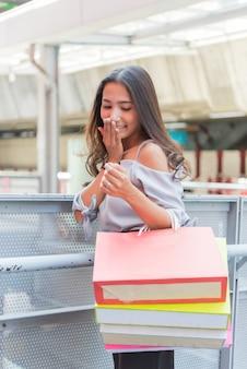 Ragazza asiatica dei bei capelli lunghi con i sacchi di carta variopinti al centro commerciale