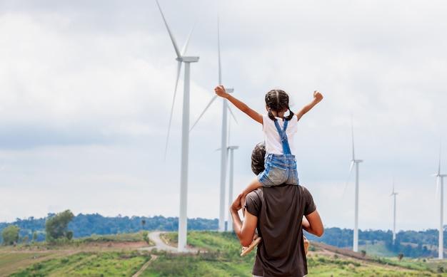 Ragazza asiatica del bambino che guida sulle spalle del padre nel campo del generatore eolico