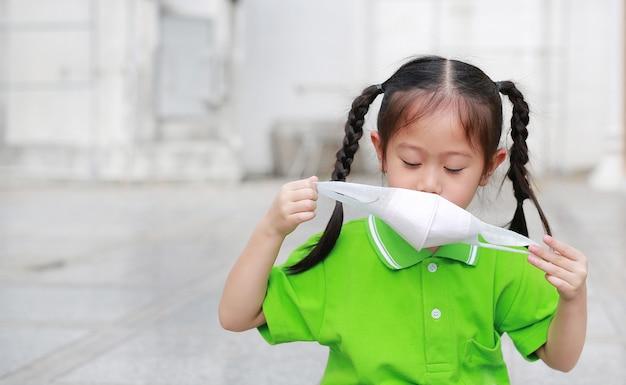 Ragazza asiatica del bambino che indossa una maschera di protezione mentre fuori contro inquinamento atmosferico.