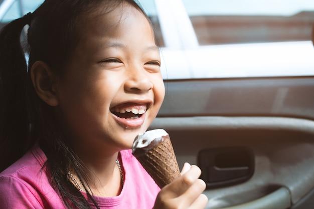 Ragazza asiatica del bambino che mangia il gelato in automobile con il sorriso e felice
