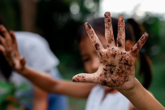 Ragazza asiatica del bambino che mostra le mani sporche dopo aver piantato l'albero nel giardino