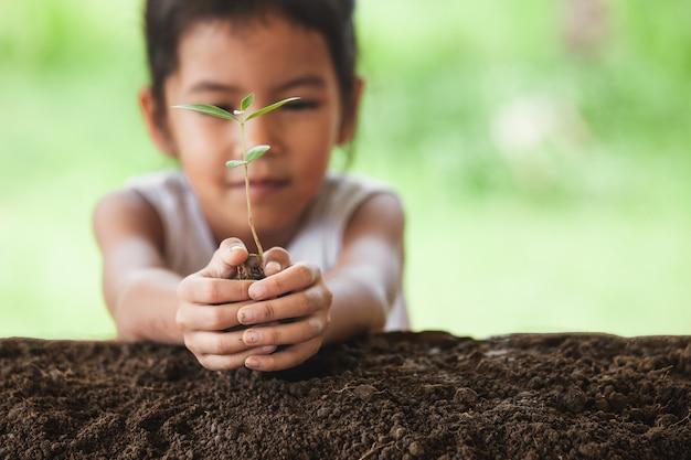 Ragazza asiatica del bambino che pianta giovane albero su suolo nero
