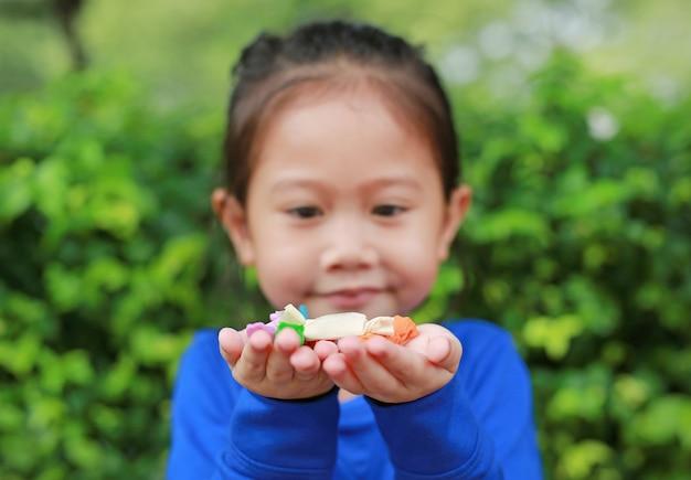 Ragazza asiatica del bambino che tiene una caramella tailandese della frutta e dello zucchero con carta colorata avvolta in sue mani. concentrarsi sulle caramelle nelle sue mani.