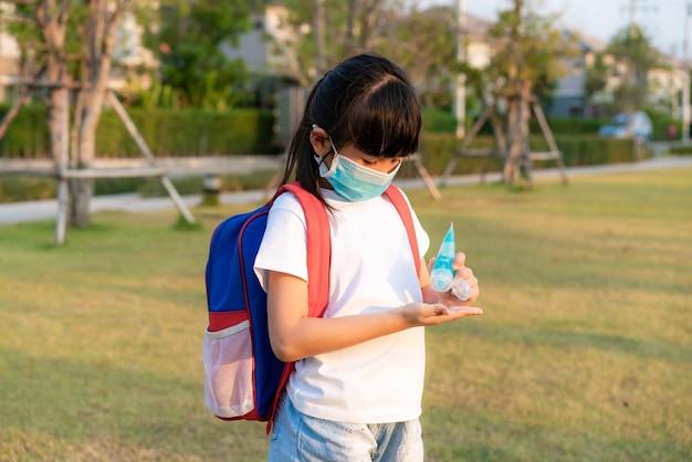 Ragazza asiatica del bambino che utilizza il gel antisettico dell'alcool, prevenzione, pulizia frequente delle mani, prevenzione dell'infezione, scoppio di covid-19, ragazza lavarsi le mani con disinfettante per le mani dopo il ritorno da scuola.
