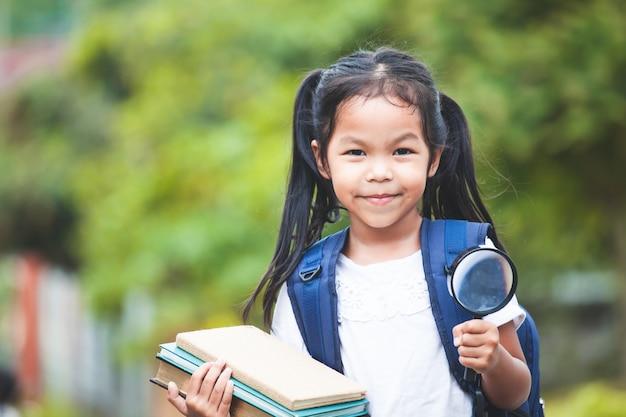 Ragazza asiatica del bambino con il sacchetto di scuola che tiene i libri e la lente d'ingrandimento pronta ad andare a scuola