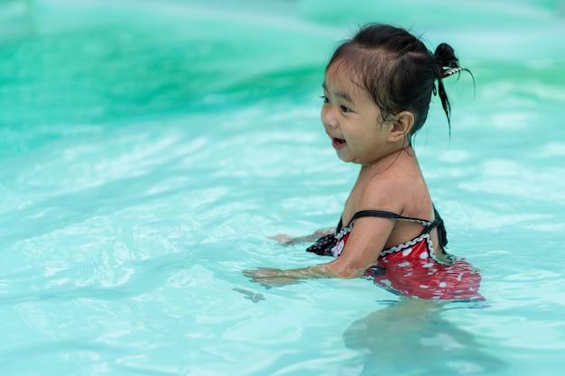 Ragazza asiatica del bambino felice nella piscina