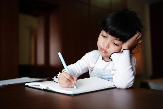 Ragazza asiatica del bambino in età prescolare che fa i compiti