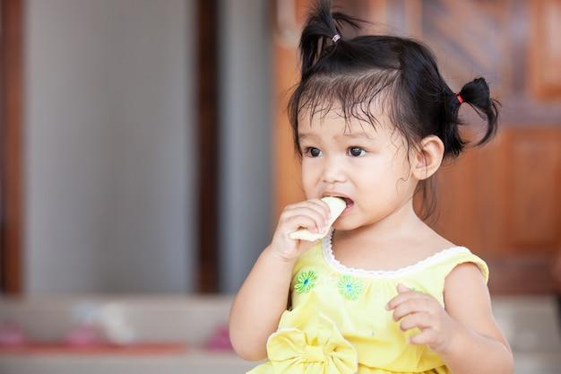 Ragazza asiatica del bambino sveglio del bambino che mangia mango