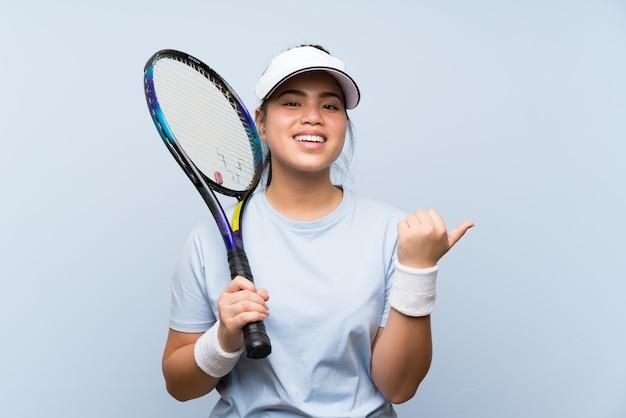 Ragazza asiatica del giovane adolescente che gioca a tennis che indica il lato per presentare un prodotto