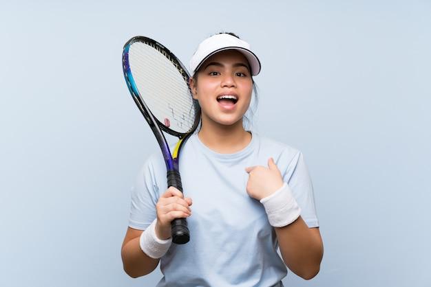 Ragazza asiatica del giovane adolescente che gioca a tennis con l'espressione facciale di sorpresa