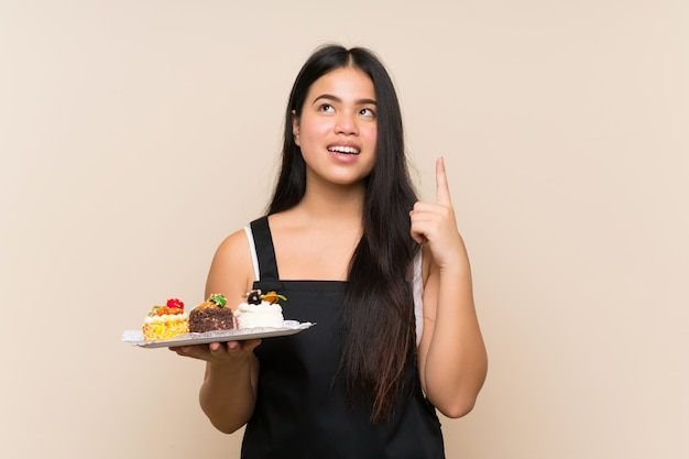 Ragazza asiatica del giovane adolescente che tiene i lotti di mini torte differenti sopra la parete isolata che intende realizzare la soluzione mentre sollevando un dito su