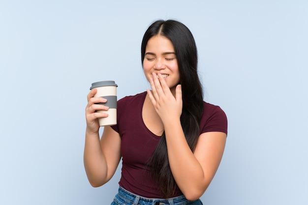 Ragazza asiatica del giovane adolescente che tiene un caffè asportabile che sorride molto