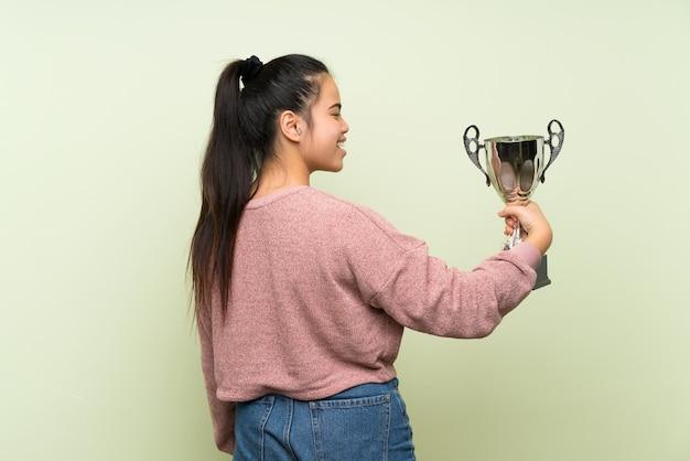 Ragazza asiatica del giovane adolescente che tiene un trofeo