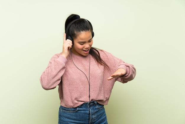 Ragazza asiatica del giovane adolescente sopra la parete verde isolata che ascolta la musica con le cuffie