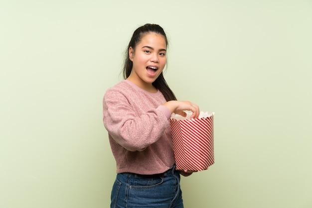 Ragazza asiatica del giovane adolescente sopra la parete verde isolata che mangia i popcorn