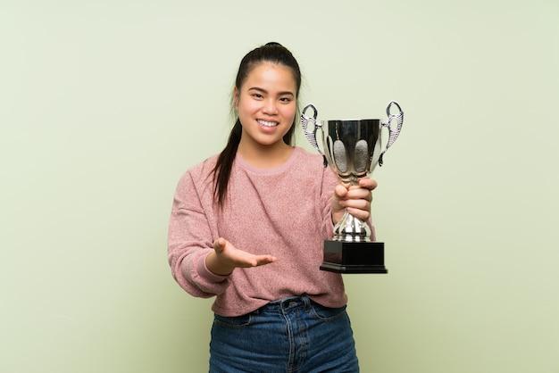 Ragazza asiatica del giovane adolescente sopra la parete verde isolata che tiene un trofeo