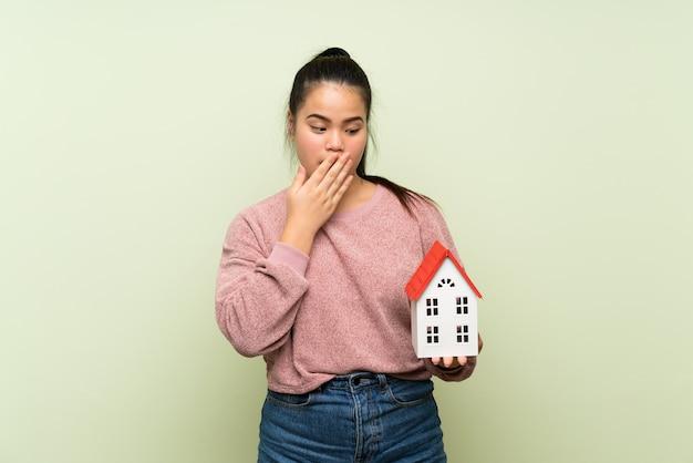 Ragazza asiatica del giovane adolescente sopra la parete verde isolata che tiene una piccola casa