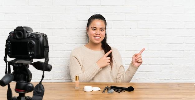 Ragazza asiatica del giovane blogger che registra un video tutorial che indica barretta al lato