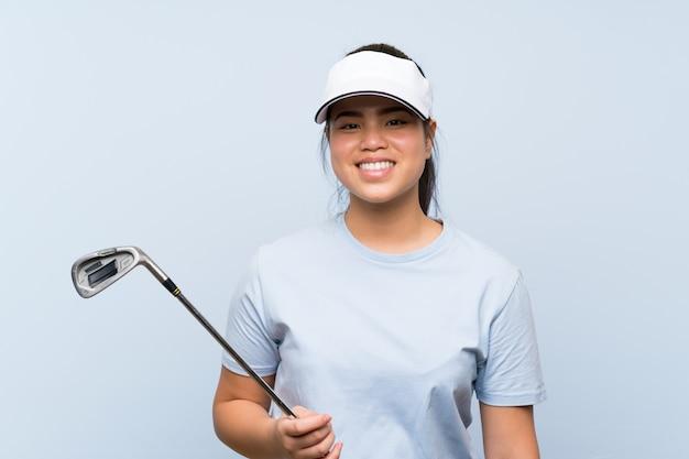 Ragazza asiatica del giovane giocatore di golf sopra fondo blu isolato