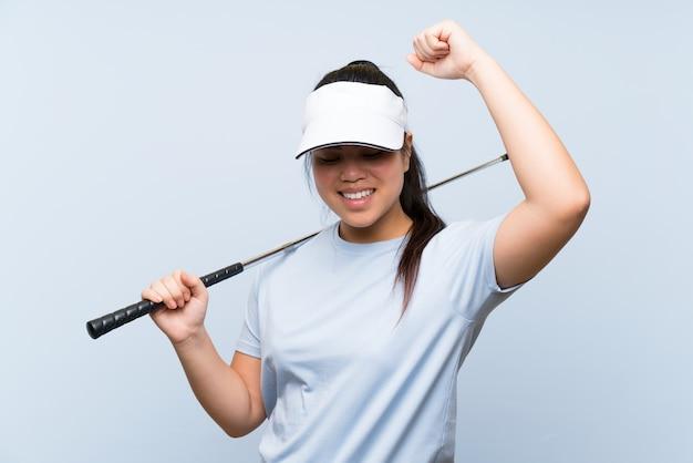 Ragazza asiatica del giovane giocatore di golf sopra la parete blu isolata che celebra una vittoria