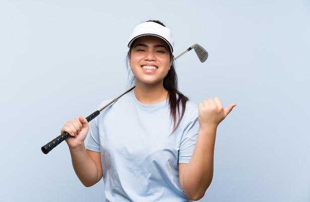 Ragazza asiatica del giovane giocatore di golf sopra la parete blu isolata che indica il lato per presentare un prodotto