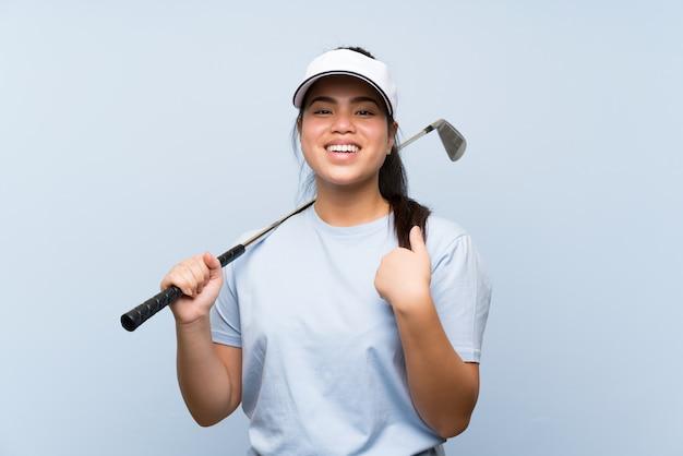 Ragazza asiatica del giovane giocatore di golf sopra la parete blu isolata con espressione facciale di sorpresa