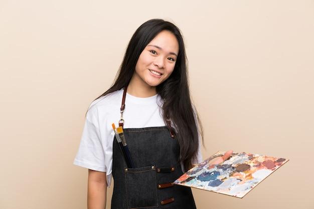 Ragazza asiatica del pittore dell'adolescente che sorride molto