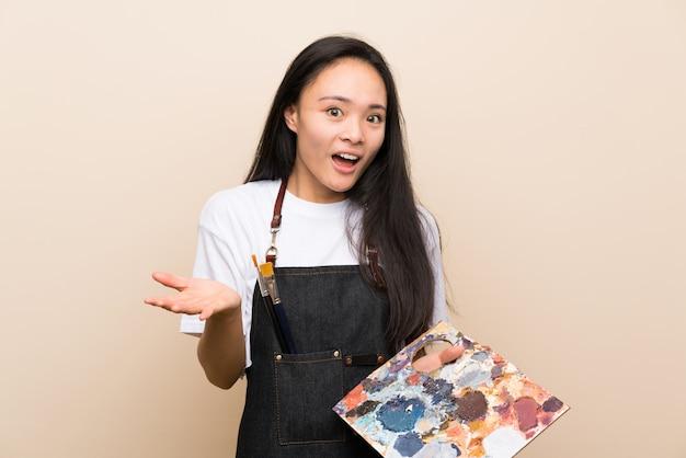 Ragazza asiatica del pittore dell'adolescente con espressione facciale colpita