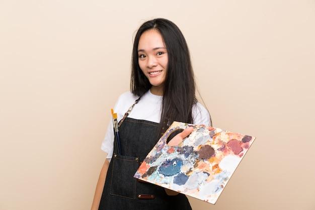 Ragazza asiatica del pittore dell'adolescente con l'espressione felice