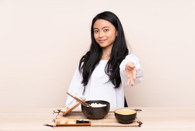 Ragazza asiatica dell'adolescente che mangia alimento asiatico isolato su beige