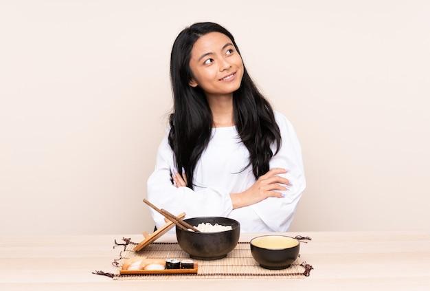 Ragazza asiatica dell'adolescente che mangia alimento asiatico isolato su fondo beige che cerca mentre sorridendo